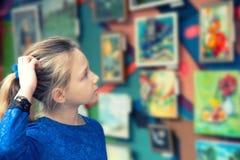 Het meisje in de kunstgalerie bekijkt kunstwerken en bewondert de werkzaamheden van grote meesters van art. royalty-vrije stock fotografie