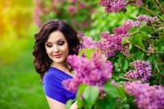 Het meisje in de lilac struiken stock foto