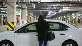 Het meisje in de ondergrondse garage zit in de auto stock footage