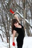Het meisje in de rode handschoenen in het hout met zijn omhoog opgeheven hand Stock Afbeeldingen