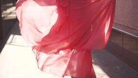 Het meisje in de rode kleding die onderaan de straat in de het plaatsen zon lopen De mening van de rug Langzame Motie stock videobeelden