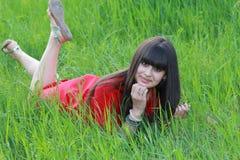 Het meisje in de rode kleding rust op groen gras Stock Afbeeldingen