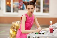 Het meisje in de roze kleding met hoofdtelefoons die in een notitieboekje schrijven Royalty-vrije Stock Foto's