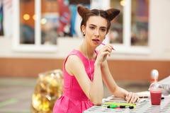 Het meisje in de roze kleding met hoofdtelefoons die in een notitieboekje schrijven Royalty-vrije Stock Foto