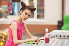 Het meisje in de roze kleding met hoofdtelefoons die in een notitieboekje schrijven Royalty-vrije Stock Fotografie