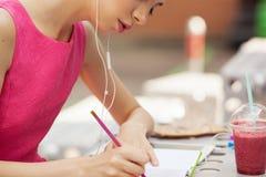Het meisje in de roze kleding met hoofdtelefoons die in een notitieboekje schrijven Stock Afbeeldingen
