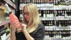 Het meisje in de supermarkt kiest alcohol stock footage