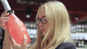 Het meisje in de supermarkt kiest alcohol stock video
