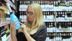 Het meisje in de supermarkt kiest alcohol stock videobeelden