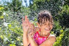 Het meisje in de tuin giet water Stock Foto's