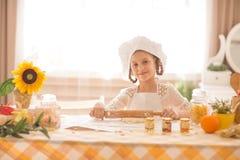 Het meisje in de vorm van een kok ontwikkelt het deeg Stock Afbeelding