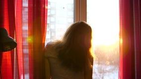 Het meisje in de vroege ochtend die zich bij het venster bevinden, opent de gordijnen De zon` s stralen gaan door het glas over e stock footage