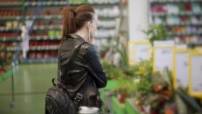 Het meisje in de winkel die zich bij de teller met ingemaakte bloemen bevinden, die op de telefoon spreken en kiest een bloem stock footage
