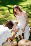 Het meisje in de witte kleding probeert om haar eerste stappen op het gazon te maken terwijl haar ouders glimlachen en haar helpe stock afbeeldingen