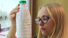 Het meisje in de zuivelafdeling kiest melk stock footage