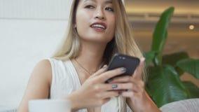 Het meisje denkt wat om in een antwoord aan vriend op smartphone app te schrijven stock videobeelden
