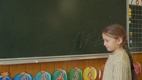 Het meisje dichtbij de raad beslist de berekeningen stock videobeelden