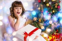 Het meisje dichtbij de verfraaide Kerstboom, houdt een wit royalty-vrije stock afbeelding