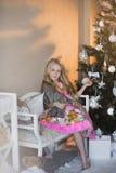 Het meisje dichtbij Kerstboom met stelt en speelgoed, dozen, Kerstmis, Nieuwjaar, levensstijl, vakantie, vakantie voor, die op sa Royalty-vrije Stock Afbeeldingen