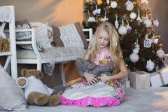 Het meisje dichtbij Kerstboom met stelt en speelgoed, dozen, Kerstmis, Nieuwjaar, levensstijl, vakantie, vakantie voor, die op sa Stock Afbeeldingen