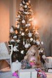 Het meisje dichtbij Kerstboom met stelt en speelgoed, dozen, Kerstmis, Nieuwjaar, levensstijl, vakantie, vakantie voor, die op sa Stock Fotografie