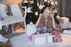 Het meisje dichtbij Kerstboom met stelt en speelgoed, dozen, Kerstmis, Nieuwjaar, levensstijl, vakantie, vakantie voor, die op sa Royalty-vrije Stock Foto
