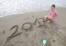 Het meisje dichtbij het overzees schrijft de tekst van het jaar 2017 op Stock Foto's