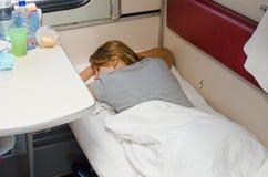 Het meisje die aan de gang op zijn maag met zijn handen achter zijn hoofd op de lagere tweedeklascoupé van de plaatsauto slapen Stock Fotografie
