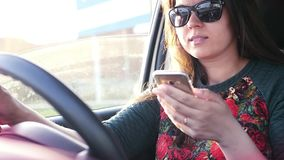 Het meisje die een auto drijven, die een auto drijven is gevaarlijk, houdend een telefoon in haar handen, bekijkend de monitor La stock video