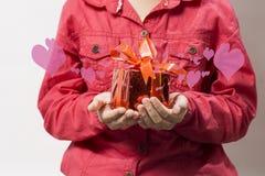 Het meisje die een glanzende rode doos met rode linten houden, wordt opgehemeld met de gloed van grootheid van liefde stock afbeeldingen