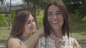Het meisje die een zilveren ketting zetten rond de halsclose-up van haar vriend Twee aantrekkelijke meisjes in lichte kleding sam stock videobeelden