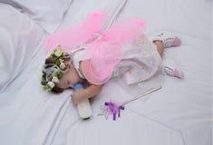Het meisje die kledingsroze met engelenvleugels dragen, slaap, eet royalty-vrije stock foto