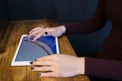 Het meisje die met een tabletcomputer werken De grafiekstijgingen Lijst, houten, achtergrondzwarte Stock Foto's