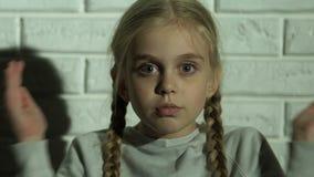 Het meisje die ogen met handen, jong geitje sluiten is bang van ouders, familiemisbruik stock video