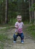 Het meisje die op de bosweg lopen Stock Afbeeldingen