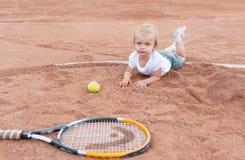 Het meisje die op de tennisbaan liggen Meisje, tennisbal en racket Royalty-vrije Stock Afbeeldingen