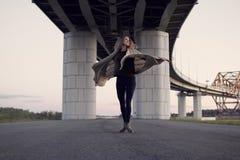 Het meisje die op de weg onder de brug over de rivier spinnen stock foto