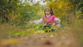 Het meisje die pret in het park hebben werpt de herfstbladeren Slow-motion stock footage