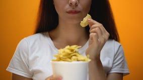 Het meisje die spaanders eten, kunstmatige aroma's in voedsel veroorzaakt verslaving, gezondheidsrisico's stock videobeelden