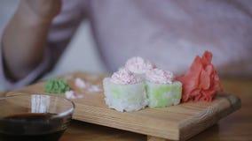 Het meisje die sushi en onderdompeling in saus in sushibar eten, sluit omhoog stock video