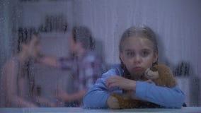 Het meisje die teddybeer koesteren, die over ouders wordt verstoord is, aanval in familie, regen strijdig stock footage