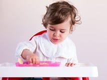 Het meisje die van de baby fruit eten stock afbeelding