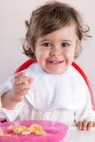 Het meisje die van de baby fruit eten Stock Foto's