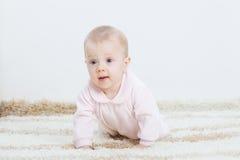 Het meisje die van de baby op het tapijt kruipen royalty-vrije stock foto