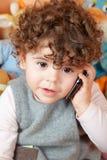 Het meisje die van de baby op telefoon spreken Stock Foto