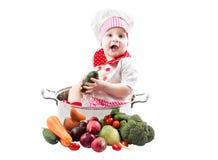 Het meisje die van de babykok chef-kokhoed met verse groenten en vruchten dragen Royalty-vrije Stock Afbeeldingen