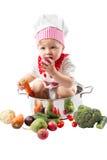 Het meisje die van de babykok chef-kokhoed met verse groenten en vruchten dragen. Royalty-vrije Stock Afbeeldingen