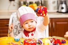 Het meisje die van de babykok chef-kokhoed met werktuigen op keuken dragen. Stock Afbeeldingen