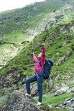 Het meisje die van de close-uptoerist zich met wapens brede open bevinden op rots royalty-vrije stock afbeelding