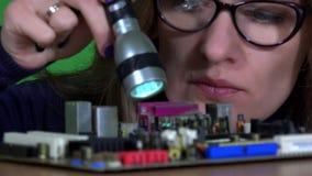 Het meisje die van de computerspecialist met glazen computermotherboard hoofdraad onderzoeken stock footage